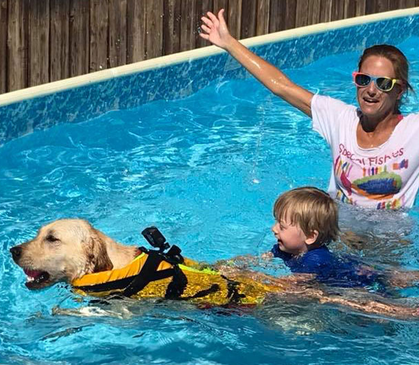 dog swimming with kids